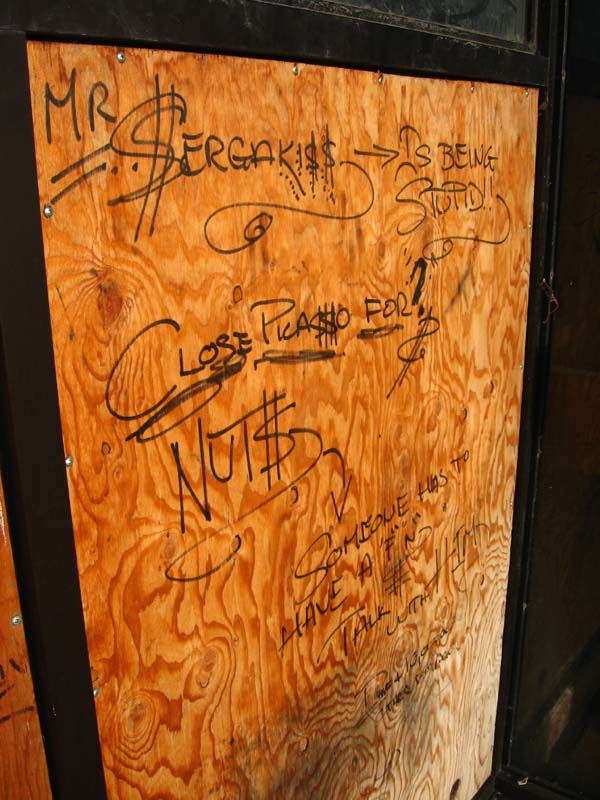 Graffiti on one boarded up window suggests one former employee's take on the restaurant-ending labour dispute.